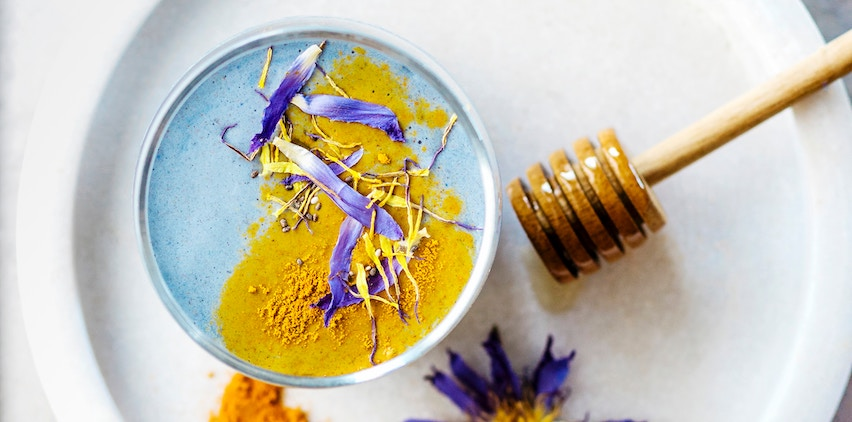 A turmeric latte with honey and edible flowers.