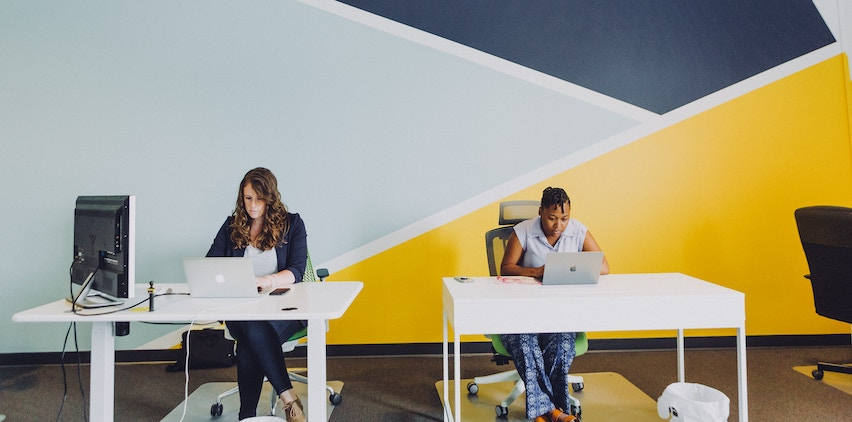 Two women sit at desks in their office.