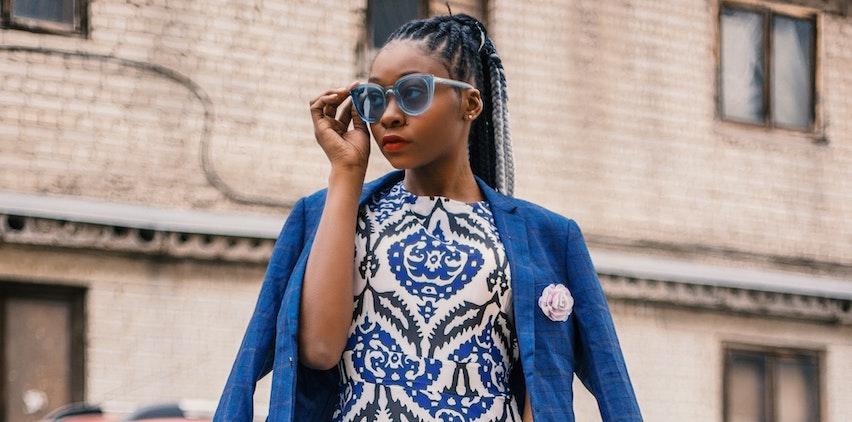 A stylish businesswoman wears sunglasses, a blazer, and a dress.
