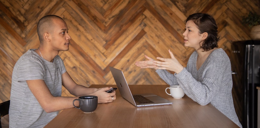 A man and women chatting in a coffee shop with a laptop.
