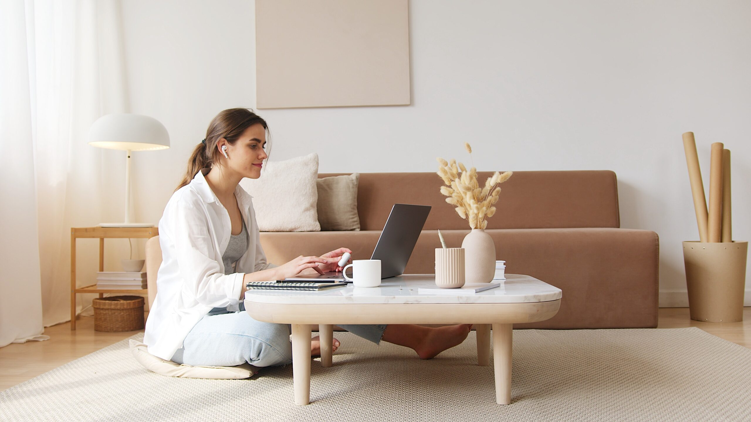 A woman working on her laptop on a coffee table