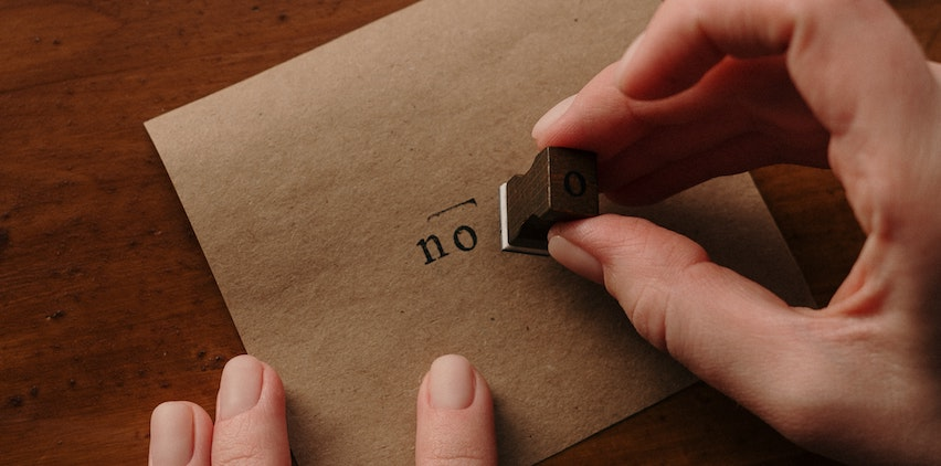 A person stamping the word no on an envelope