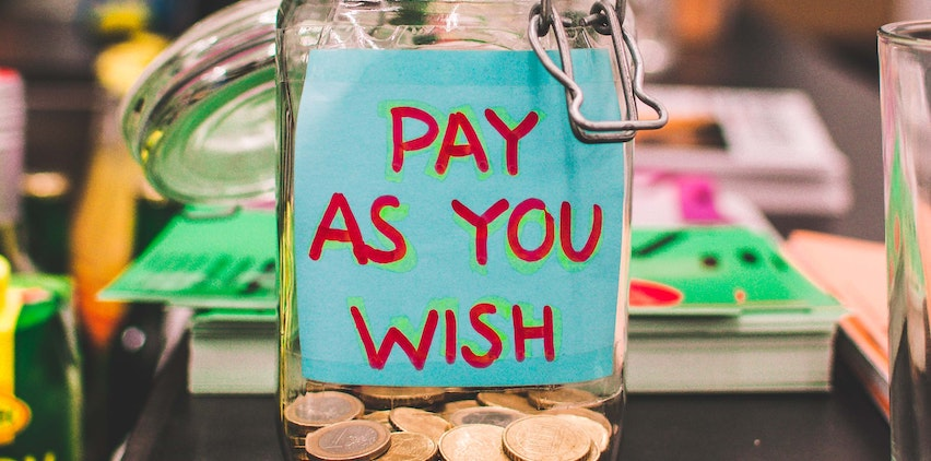 A jar full of coins that says pay as you wish