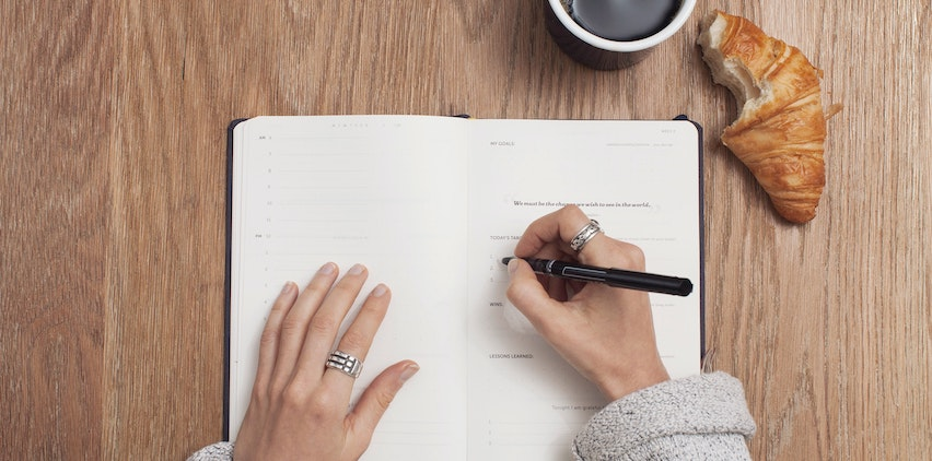 A woman writing in her planner