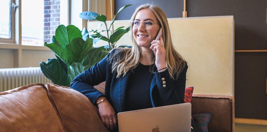 Woman wearing a blazer on laptop, talking on phone