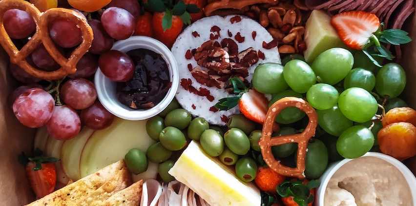 Charcuterie board with fruit, pretzels, and cheese
