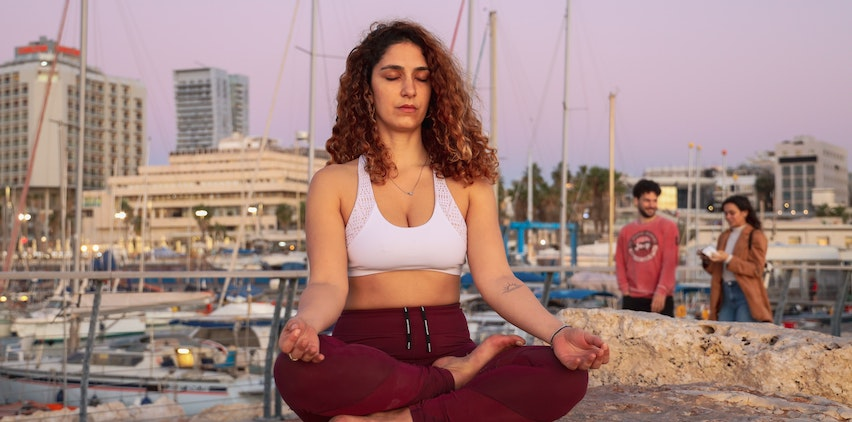 Woman practicing meditation in a marina