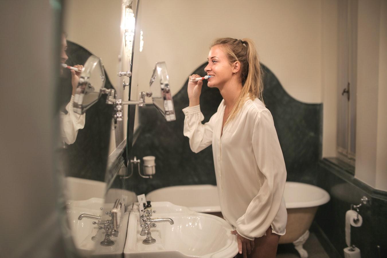 A woman brushing her teeth in the bathroom