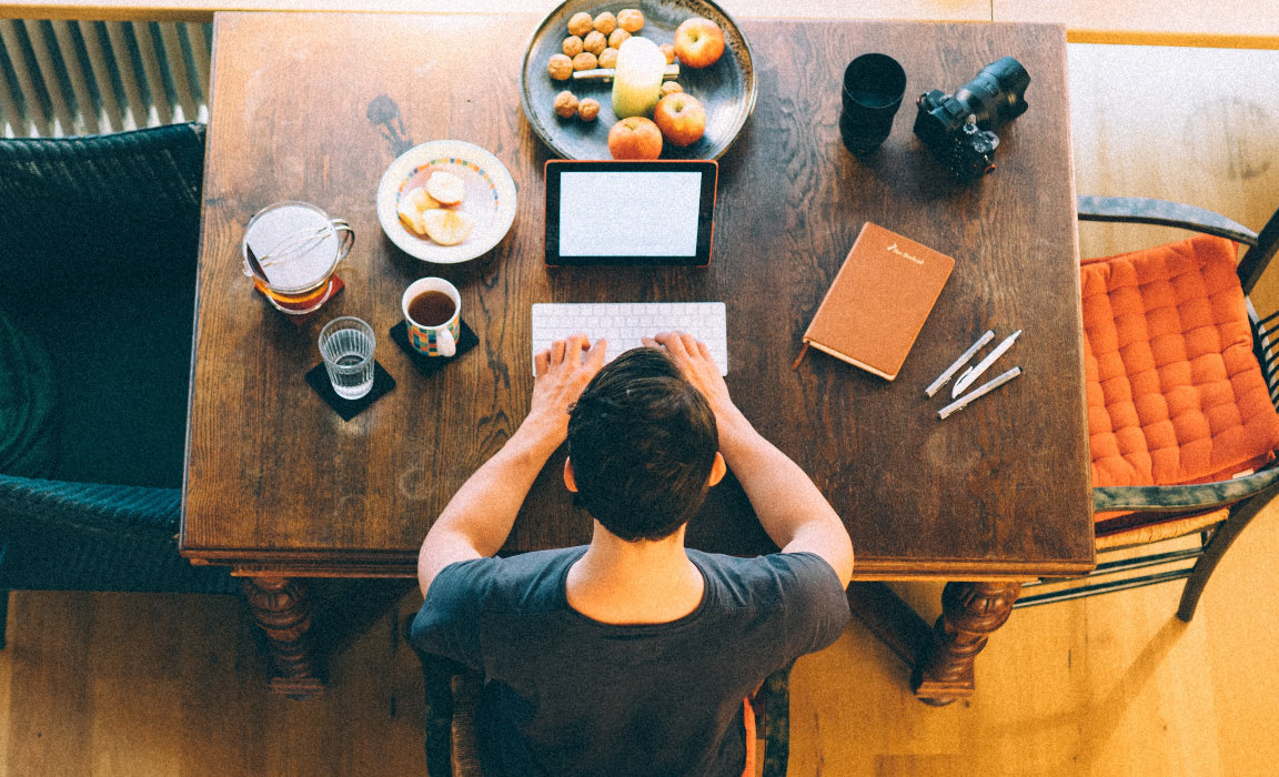 A man working at a kitchen table in the morning.