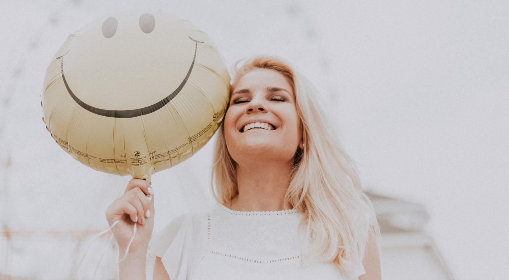 A woman smiling with a smiley face balloon