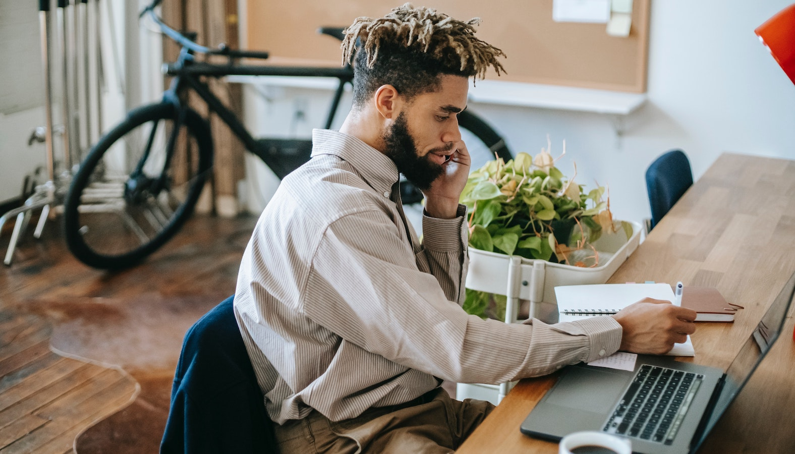 A man working on a laptop while talking on the phone.